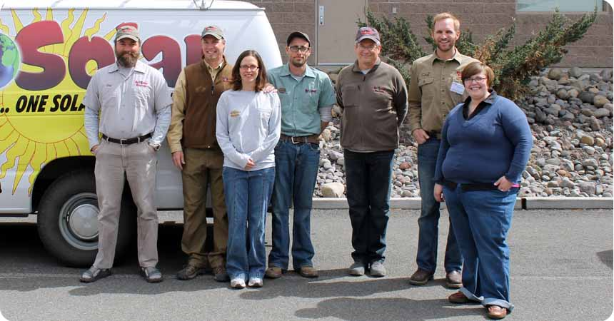 EcoSolar and Electric employees standing in front of their van.