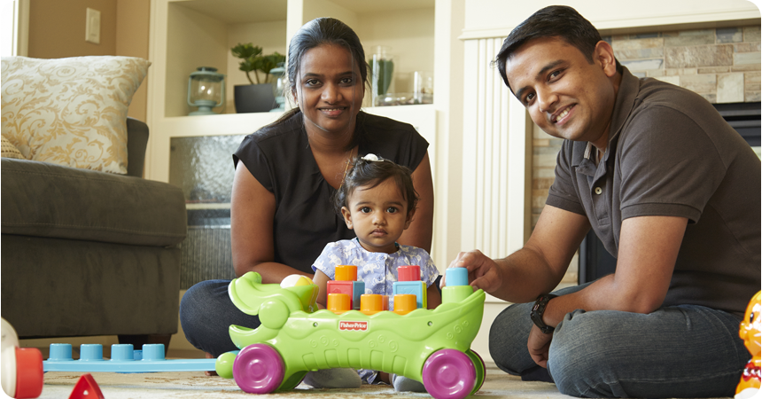 Couple with their small daughter sitting and playing on the floor of their home.