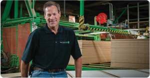 Timber Products employee sitting in front of stacks of lumber.