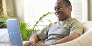Man sitting on couch while working on a laptop.