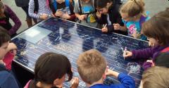 Students at Arleta School sign a demonstration solar panel.