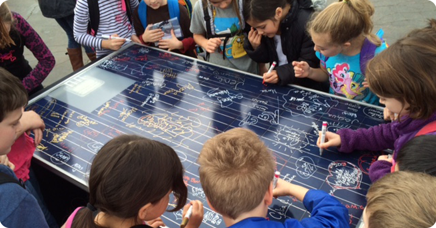 Students at Arleta School sign a demonstration solar panel.