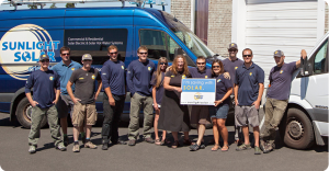 the Sunlight Solar energy team standing in front of a van