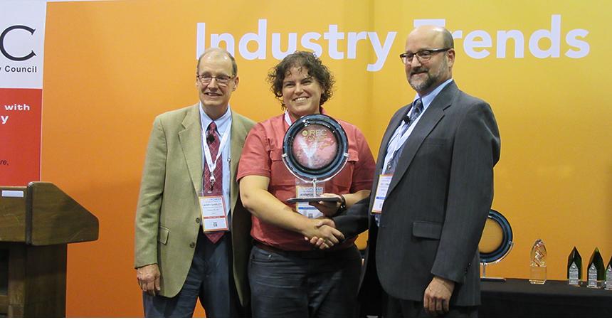 an Energy Trust employee, Jeni Hall, receiving a trophy