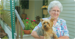 an elderly woman and her dog in front of her home