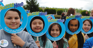 children smiling holding up net zero hero signs
