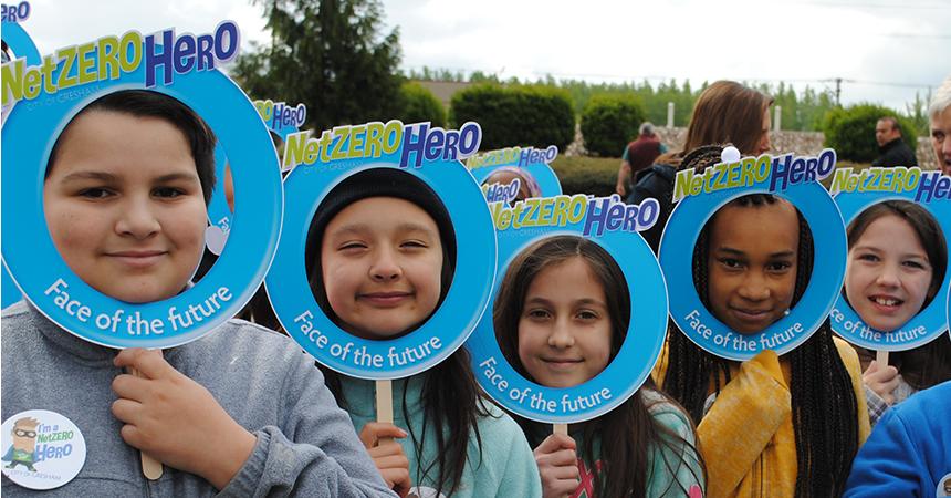 children smiling holding up net zero hero signs