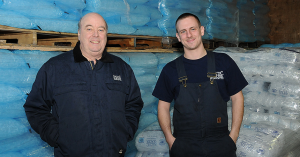 two men in blue standing infront of hundreds of bags of ice