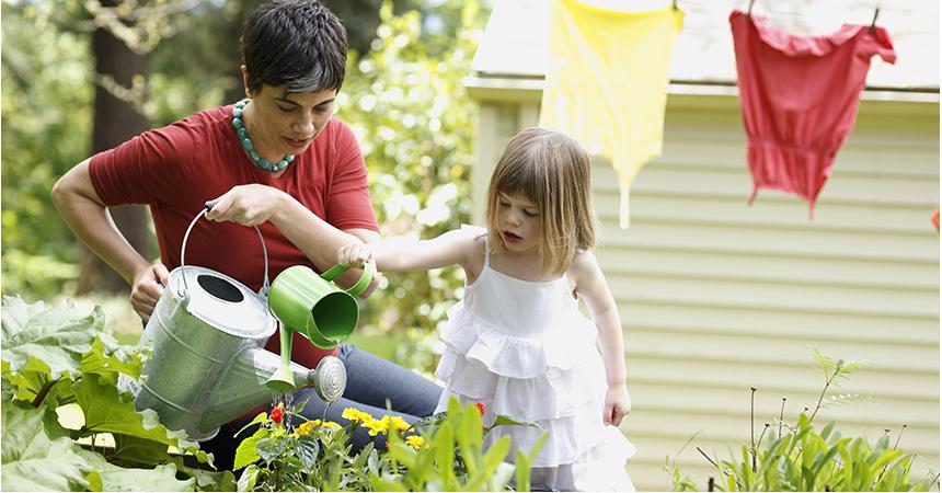 Mother and daughter watering garden plants