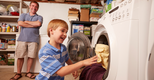 smiling father watching his laughing son do laundry