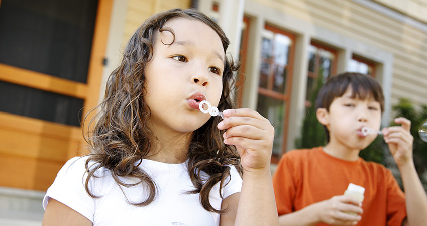 a boy and girl blowing bubbles in front of their home