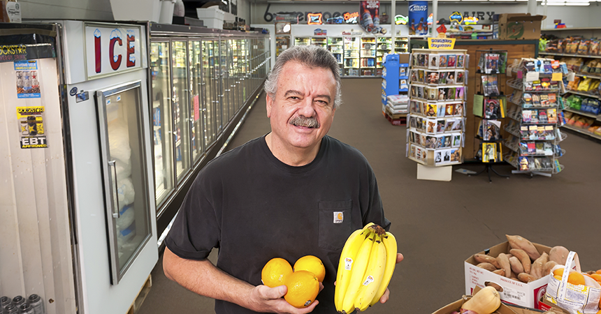 man holding oranges and bananas in grocery store