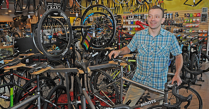 a man in a bikeshop, surrounded by colorful bicycles