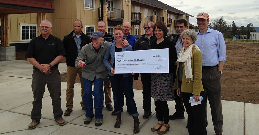a group of recipients holding a big check in front of the completed Iron Horse Lodge
