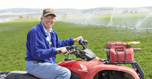 a woman on a bright red 4-wheeler, in a green farm field