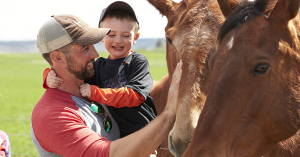 farmer and young boy petting a brown horse