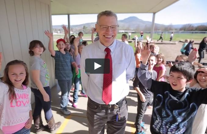 smiling school principal surrounded by waving students