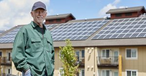 man in ballcap standing in front of multifamily building with solar panels on the roof