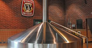 a large stainless steel vat in a brick building with the widmere logo in the background