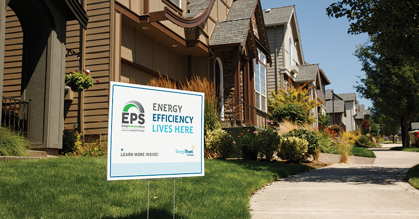 "a yard sign saying ""energy efficiency lives here"" in the front yard of a home"