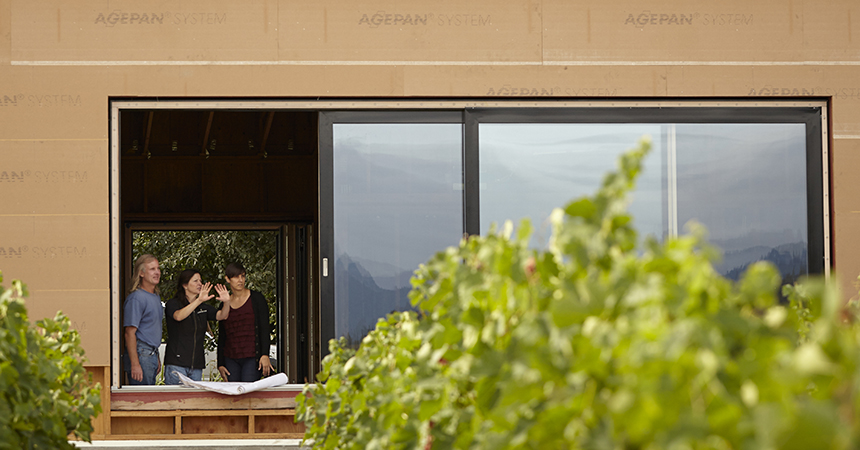 a woman gesturing with her hands to a couple at the Cowhorn Vineyard