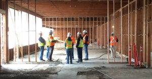 a construction team with hardhats in a wood frame building in progress