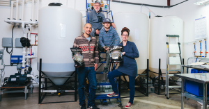 a team of Yerba Buena employees displaying their product in their growing facility