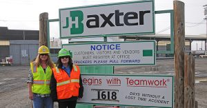 two women wearing hard hats in front of J.H. Baxter sign