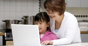a mother and daughter smiling working on a laptop computer