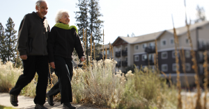 an older couple walking in front of a multifamily building
