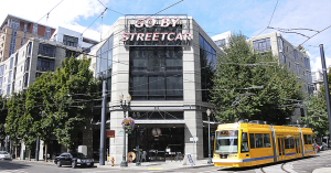 """a neon sign saying """"go by streetcar"""" with a yellow street car passing by"""