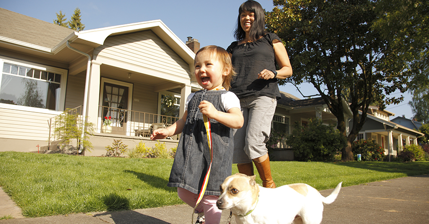 smiling woman and toddler walking a dog in front of their house