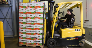 Trask Pernetti, a warehouse trainer with Organically Grown Company, moves a pallet of bananas in a banana ripening room.