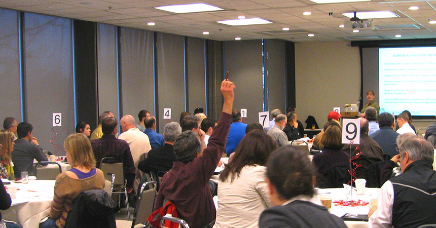 large training room filled, a man with a raised hand asking the speaker a question