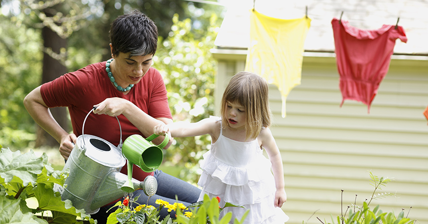 Mother and daughter watering garden plants