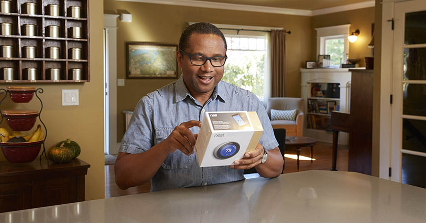 man reading the back of a smart thermostat box in his home