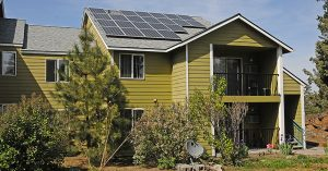 Green apartment building with solar panels on roof