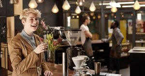 woman drinking a cup of coffee in a brightly lit coffee shop