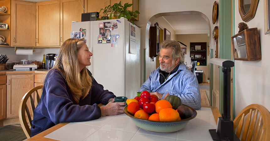 A man and a woman sitting in a kitchen talking with a big bowl of colorful fruit on the table.