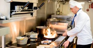 Chef standing at stove top holding a pan with flames arising out of it.