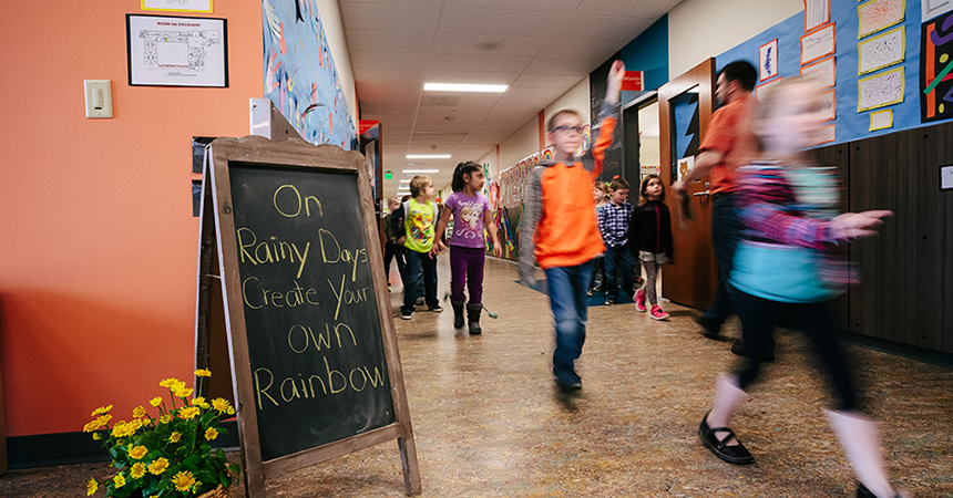 """Kids walking down a hallway in a school with a chalkboard sign that says, """"On Rainy Days Create Your Own Rainbow"""""""