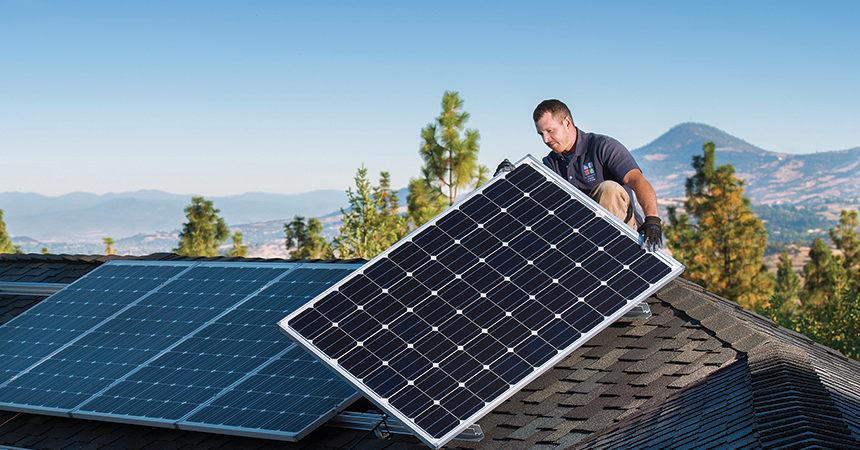 a trade ally installing a solar panel on a home