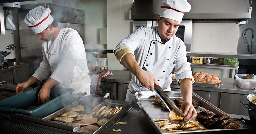 two chefs in a restaurant kitchen cooking chicken on a grill
