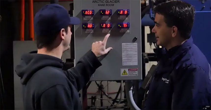 two men working on a electrical box in a cold storage facility