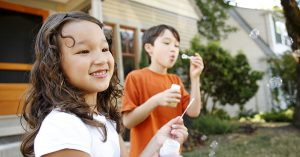 two children outside a house blowing bubbles
