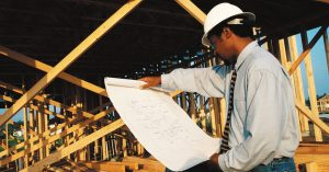a contractor looks over building blueprints on a job site