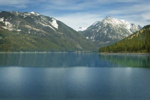 a picture of snow capped mountains behind a lake, the wallowas