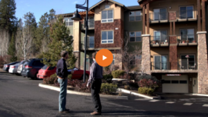 two men talking outside a multifamily property