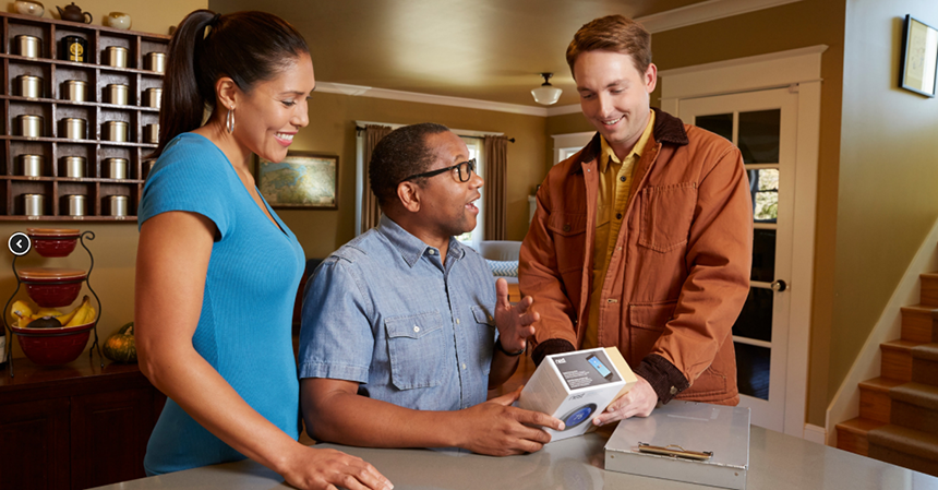 three people excitedly opening a new thermostat