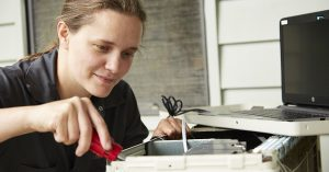 a woman using a screwdriver on some equipment